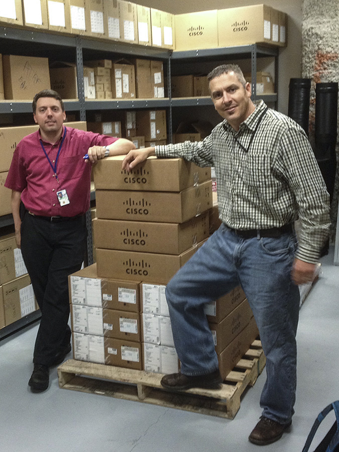 Two men standing by a pallet of boxes.
