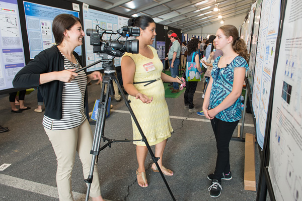 Rebecca Matthews, Werner H. Kirsten student intern (right), was filmed by reporter Mallory Sofastaii as part of a WHAG-TV video highlighting the Spring Research Festival. Lanessa Hill, public affairs specialist, U.S. Army Garrison, provides some media coaching.
