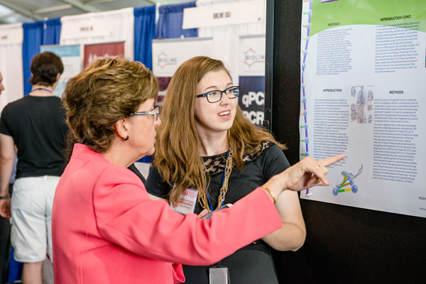 Frederick County Public Schools (FCPS) Superintendent Terry Alban speaks to NCI at Frederick student intern Dominique Brown about Brown's poster.