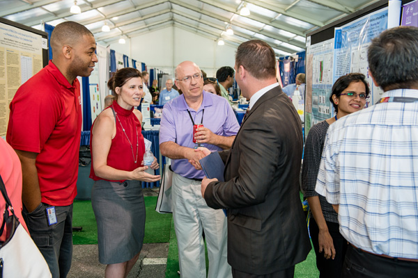 Craig Reynolds (center), associate director, NCI, greets Mike Markoe, deputy superintendent, FCPS, as Markoe toured the Spring Research Festival. Also pictured are (from left) Jim Cherry and Marsha Nelson-Duncan.