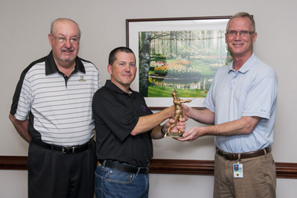 Dom Esposito (center) receives the most valuable player award for the Leidos Biomedical Research team from team captains Dave Heimbrook (right) and Denny Dougherty. Photo by Joe Meyer, Staff Photographer.