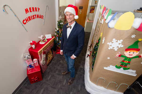 """Frank Blanchard, director of Public Affairs, Frederick National Laboratory for Cancer Research, stands amid ATRF E3200's """"Candyland"""" decorations."""