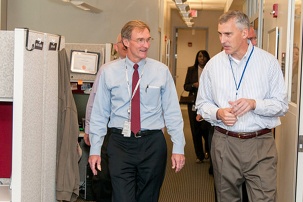 Leidos Chief Executive Officer Roger Krone (left) tours NCL with Scott McNeil. File photo.