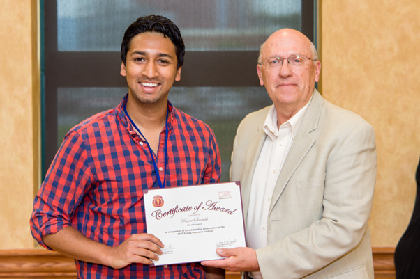 Ranu Sinniah receives his award for Outstanding Presentation at the Scientific Symposium from NCI Associate Director Craig Reynolds, Ph.D.
