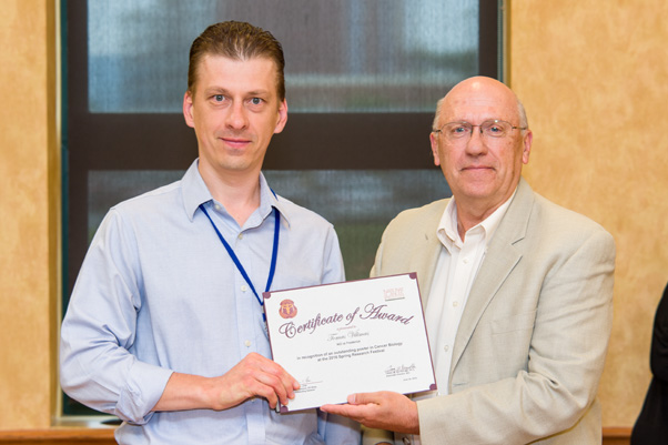 Tomas Vilimus receives his award for an Outstanding Poster from NCI Associate Director Craig Reynolds, Ph.D.