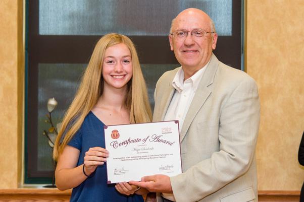 Werner H. Kirsten Student Intern Maya Swiderski receives her award for an Outstanding Poster from NCI Associate Director Craig Reynolds, Ph.D.