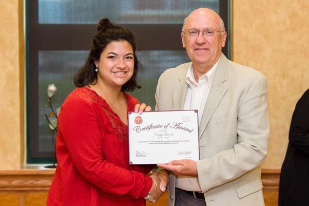 Werner H. Kirsten Student Intern Emily Burnett receives her award for an Outstanding Poster from NCI Associate Director Craig Reynolds, Ph.D.