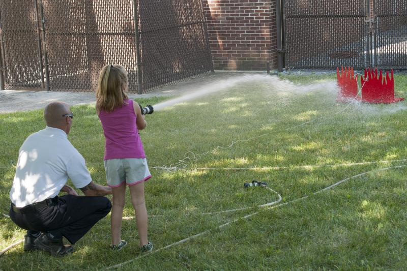 With help from a firefighter, kids used a real hose to put out a simulated fire.