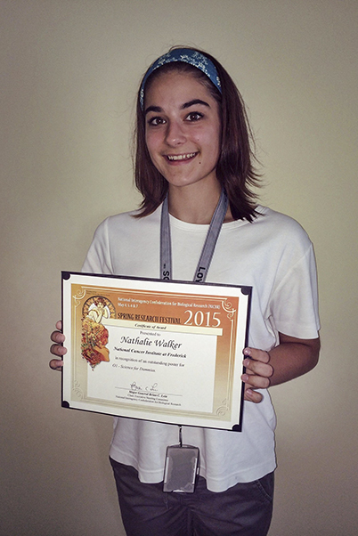 Walker holding her Outstanding Poster award from the 2015 Spring Research Festival.