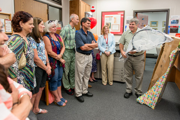 Colleagues watch as Wiltrout receives a fishing net during his retirement party.