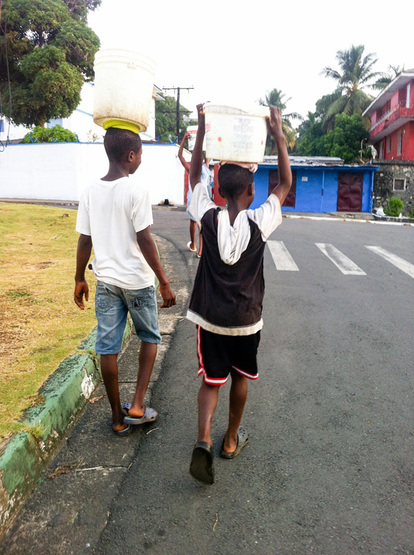 Two boys carrying water down a street in Monrovia, Liberia. Photo courtesy of Helene Highbarger, ADRD.