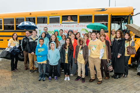 Tour group standing in front of a school bus.