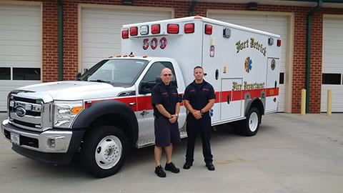 Two members of Company 50 pose with their ambulance.