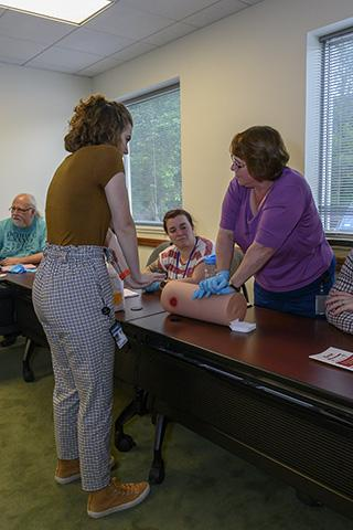A participant practices on a training dummy while Emme Tissue instructs