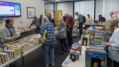 Photo: a small crowd of visitors peruses rows of tables lined with books at the Book and Media Swap