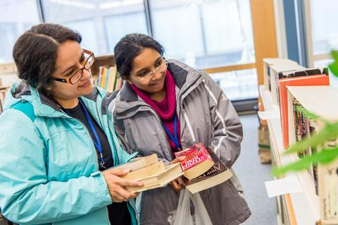 Two women browse books at the Book Swap