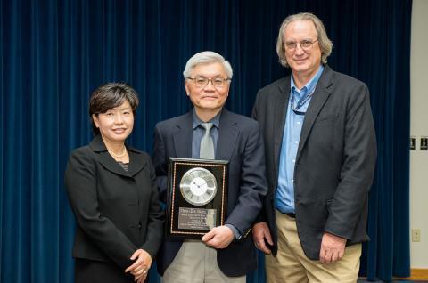 Three people with an award.