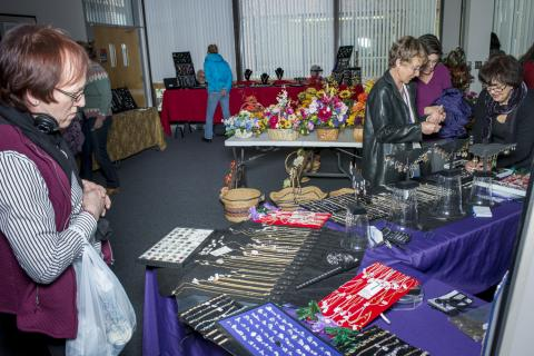 Employees browsing vendor tables at Holiday Market