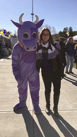 Photo of Maddie Hurwitz with Williams College's mascot, Ephalia, a large purple cow