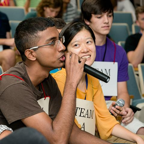 two students, one talking into a microphone.