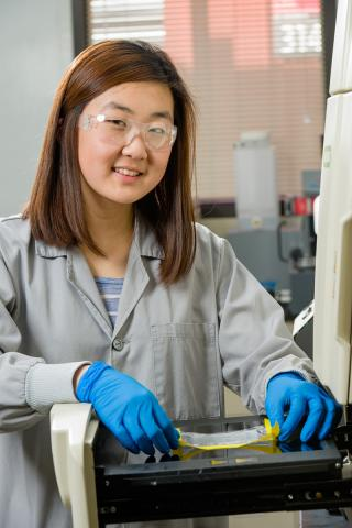 Photo of Allison Kang smiling while working with a scientific instrument in the laboratory