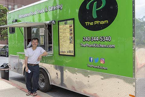 Photo of An Pham, owner of The Pham, standing in front of his bright green food truck