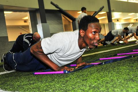 A man does a pushup as part of an exercise class.