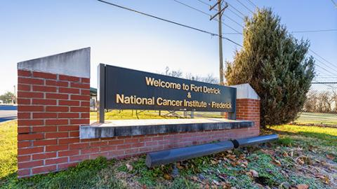 "Photo of a large brick and metal sign beside a fence. The sign says, ""Welcome to Fort Detrick & National Cancer Institute - Frederick"""