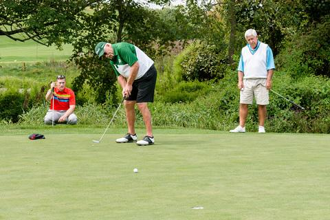 Man putts as two players watch