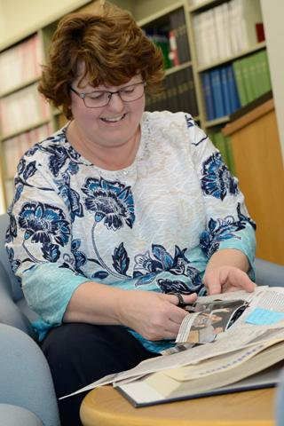 Library Technician Pamela Noble prepares a scrapbook.