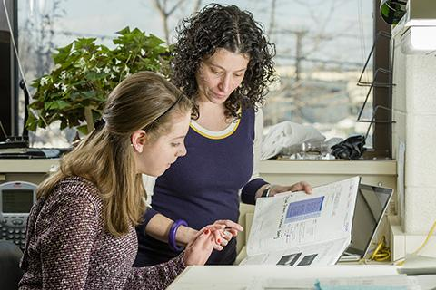 Photo of a student and her mentor sitting and reviewing documents at a desk