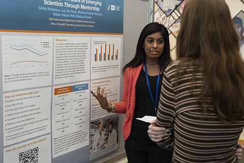 Photo of intern Ishika Srivastava standing at her poster and explaining her project to another student