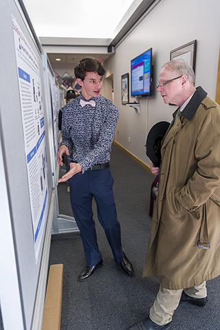 A high school student gestures to a poster hanging on a board as a senior scientist in a peacoat listens