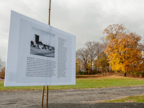 One of the signs detailing the history of Fort Detrick, with a yellow tree in the background.