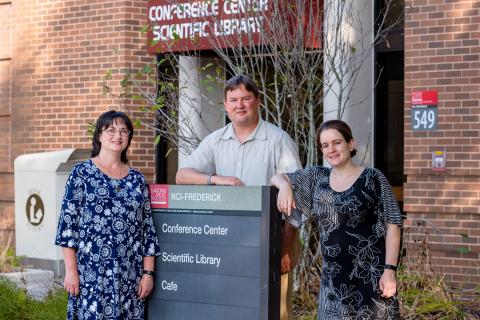 Three members of the Scientific Library staff stand outside of the building.