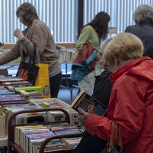 Women browsing books at the 2018 book and media swap.