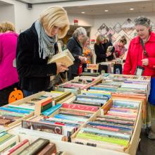 A woman checks out with her new books at the 2017 Book and Media Swap.