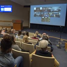 Employees watch the telecast in the Building 549 auditorium.