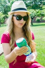 Julianne Heberlein, Werner H. Kirsten Student Intern, is wearing a protective hat and sunglasses as she applies sunscreen to prevent overexposure to the sun's UV rays.