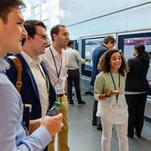 Visitors to the 2019 Tech Showcase talk to a poster presenter.