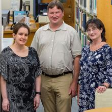 Three members of the Scientific Library staff are pictured inside the library.