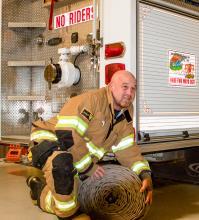 Fireman kneeling by truck.