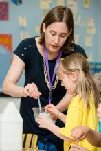 Volunteer stirring liquid in a cup while child looks on