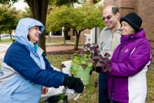 Howard Young and Dolores Winterstein receiving a plant from a participant