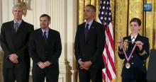 Schiller, Lowy, President Obama, and military aide holding medal at ceremony.