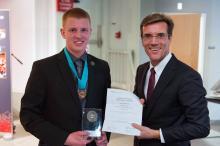 Two men holding an award.