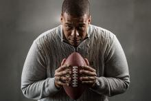 Studio portrait of James Cherry with a football.