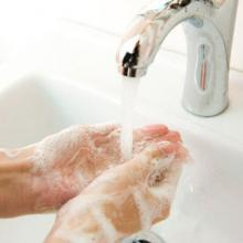 an image of hands being washed beneath a sink.
